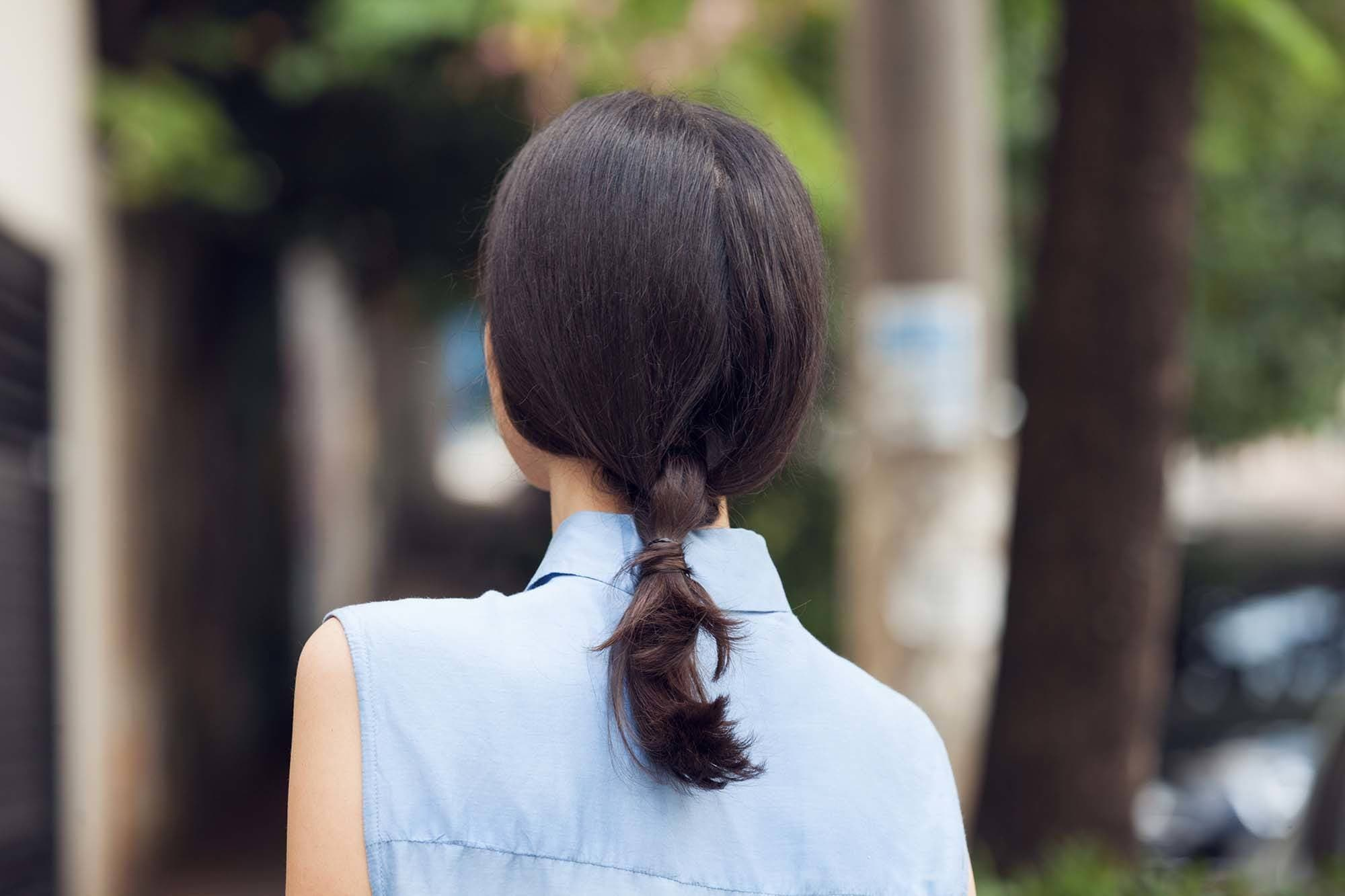 Brunette woman wearing shoulder length hairdos knotted low ponytail.