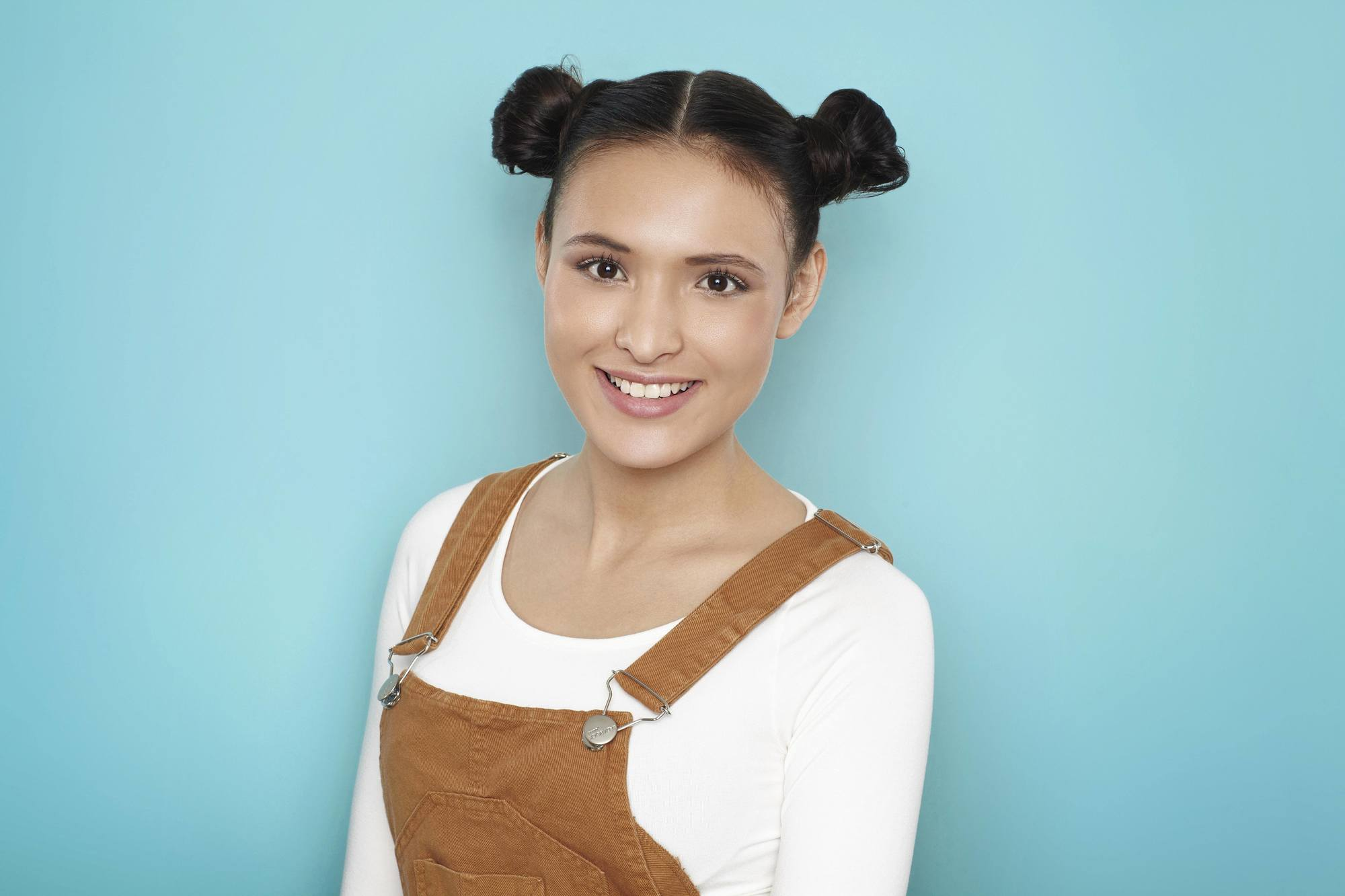 Brunette woman wearing shoulder length hairdos space buns and center part.