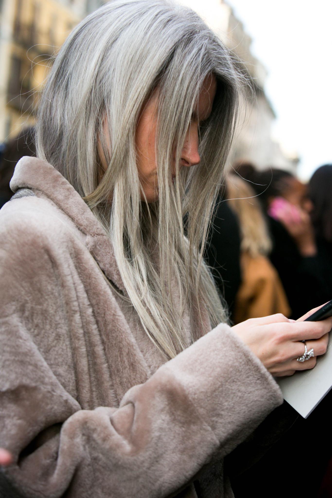 Woman with silver brown hair streaks in silver hair.