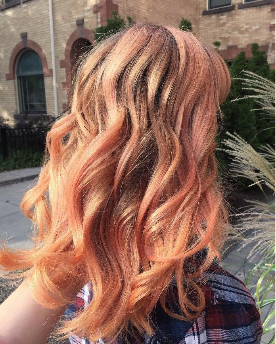 Woman with strawberry hair streaks in blonde hair.