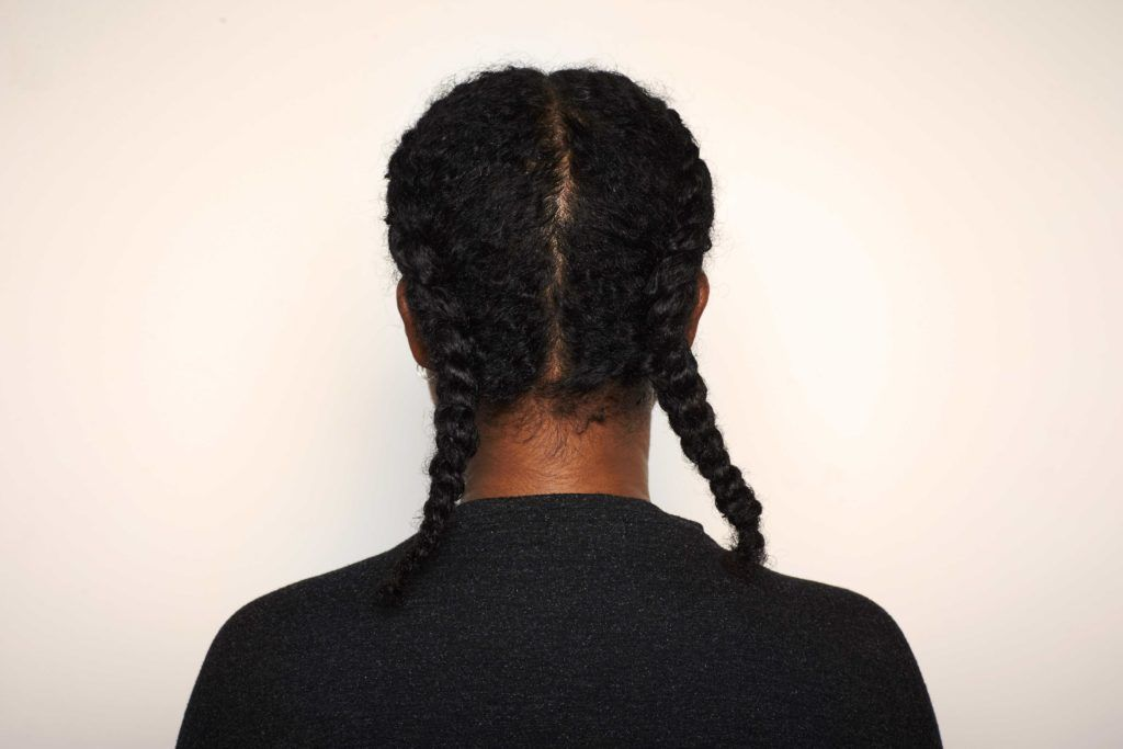 Woman using transitioning hairstyles to grow out chemically straightened hair. Boxer braids.