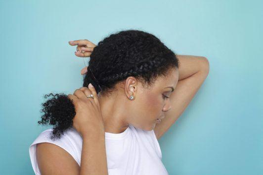 woman creating low ponytail on natural hair braids