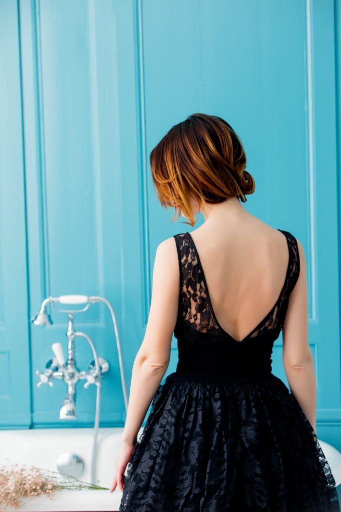 a woman with short hair updo wearing black dress standing in front of blue wall
