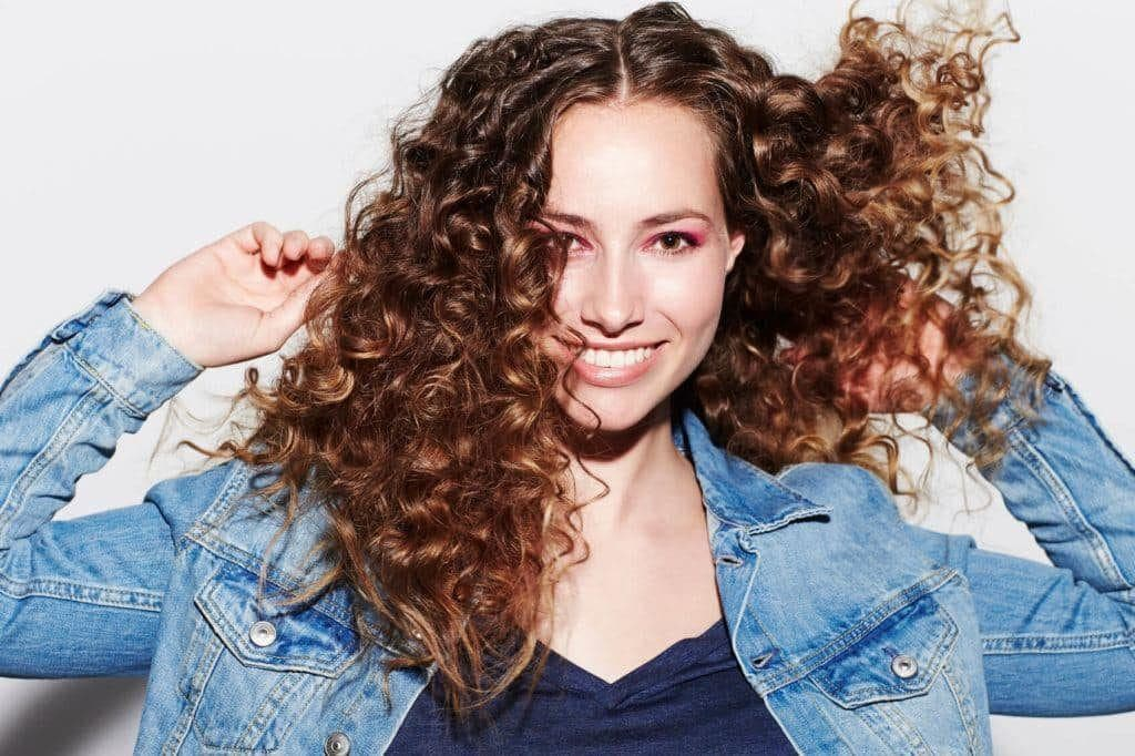 a close up shot of a woman with curly hair wearing denim oufit