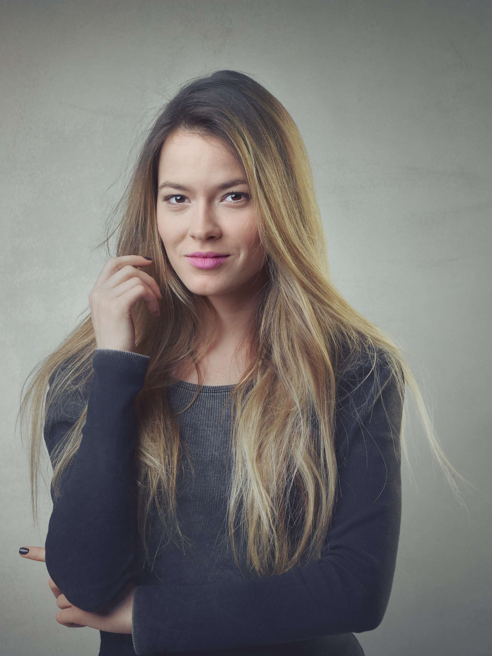 a smiling woman with ombre hair wearing a black sweater