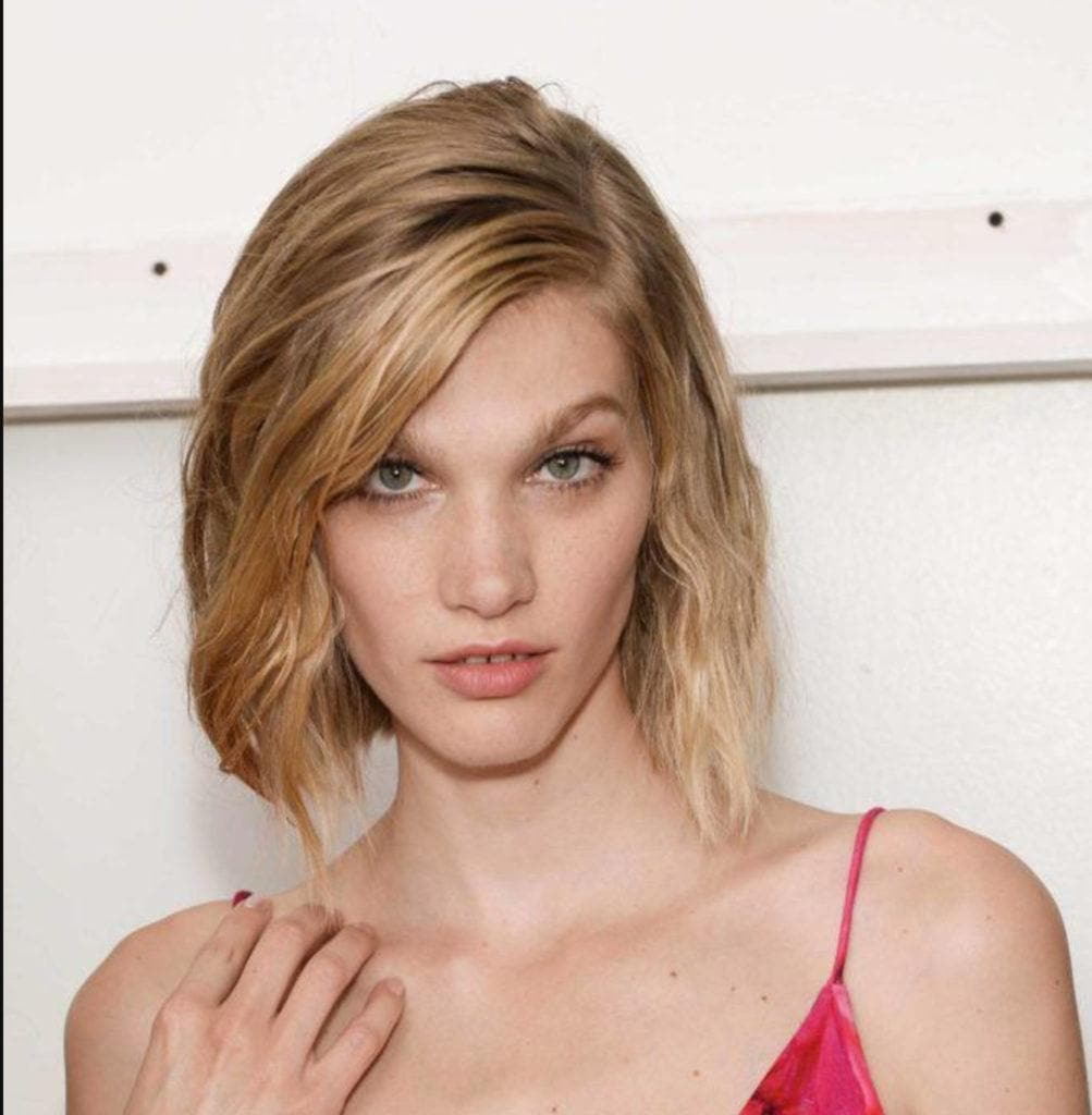 a closeup look of a blonde woman with short hair wearing dress