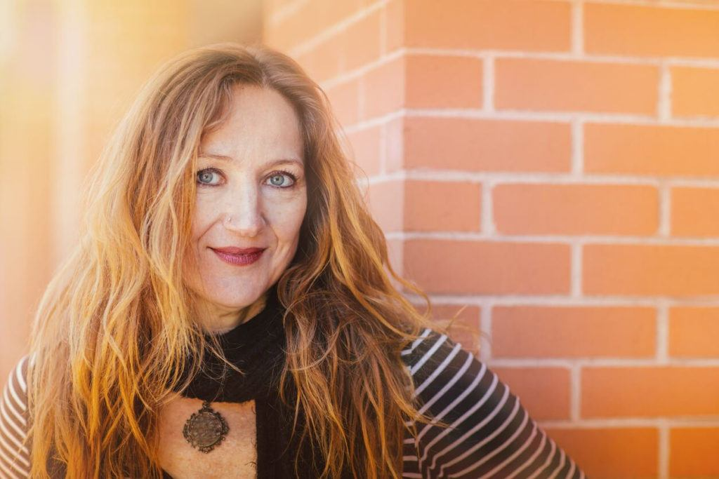 a senior woman sunlighted wavy long hair on brick wall