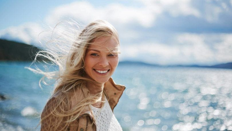 a blonde woman smiling on the beach