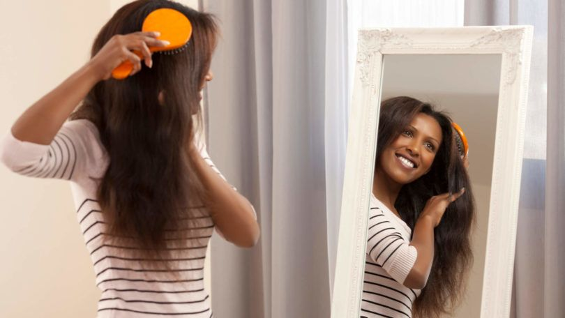 a black woman brushing her long hair in her bed room