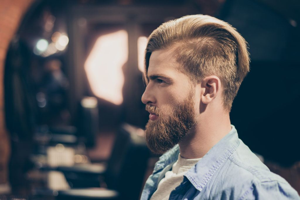 a handsome slick back undercut hairstyle a man in a barbershop