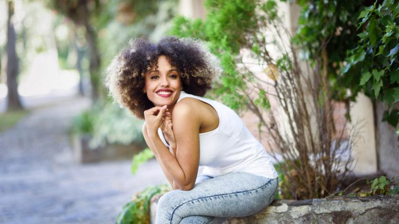 a cute afro woman sitting in a garden