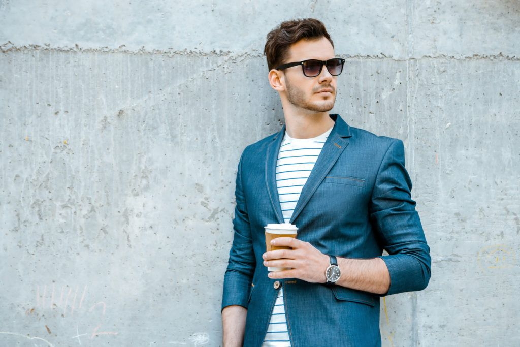 a well stylish man holding a coffee cup on a wall