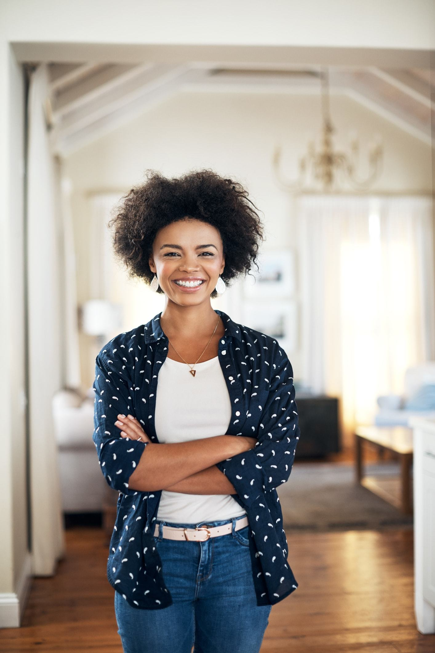 an afro curly woman posing inside a living room