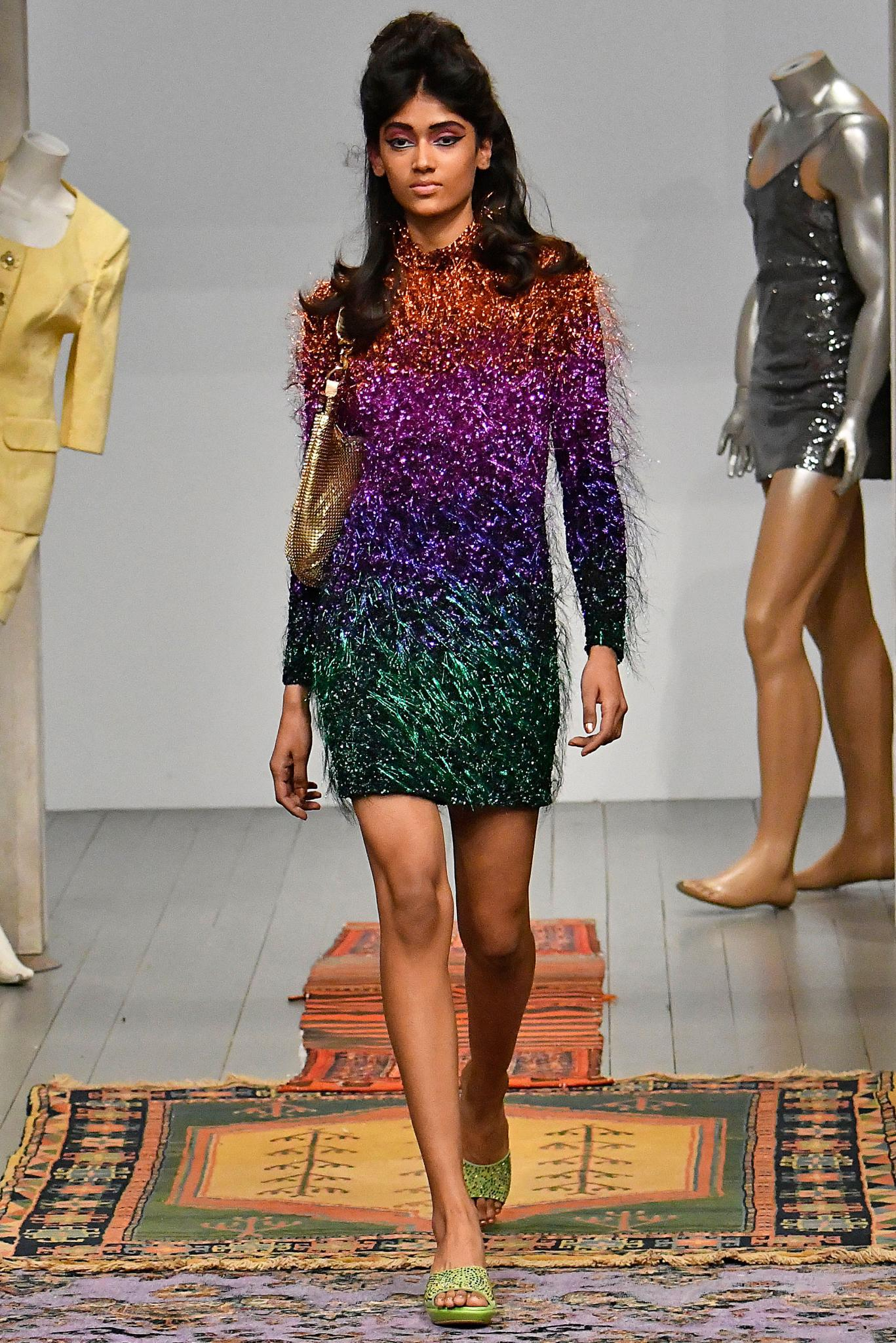a beautiful female fashion model walking on a runway