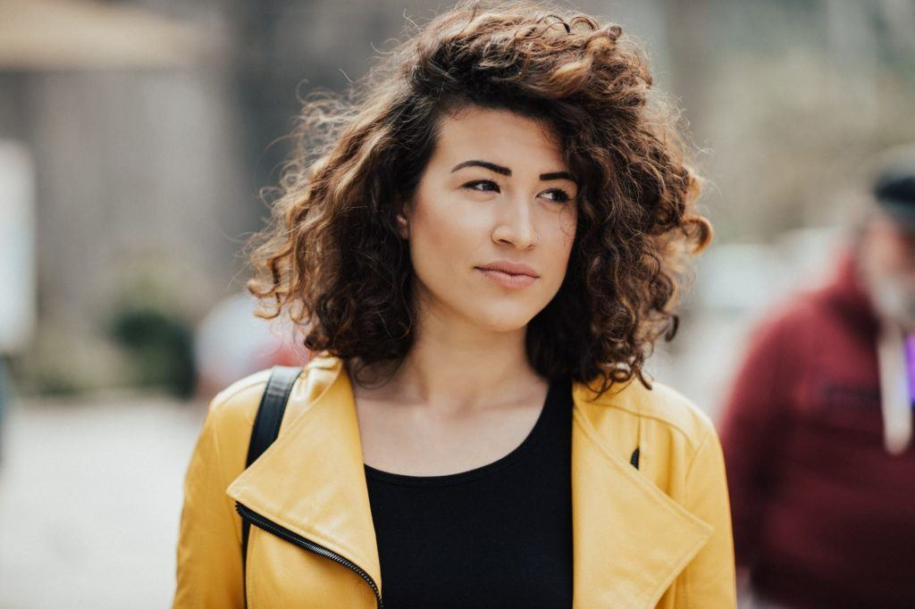 a messy hair woman looking away on a street