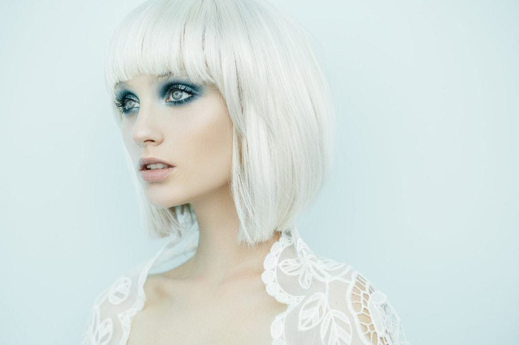 a bleached hair woman in a wedding dress on the light blue background