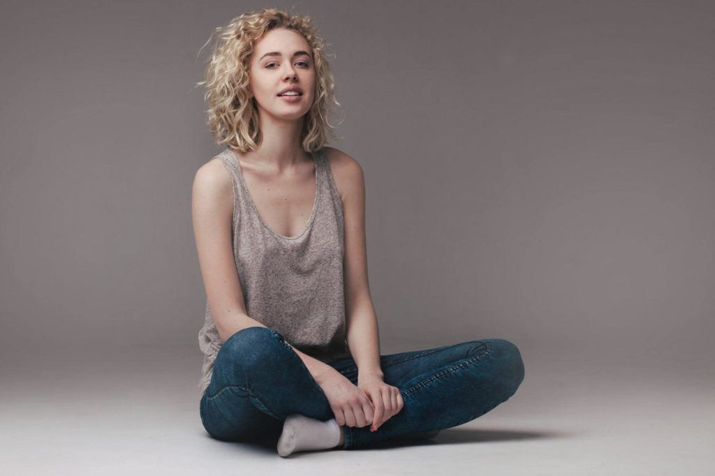 casual look of a woman wearing denim pants on grey background