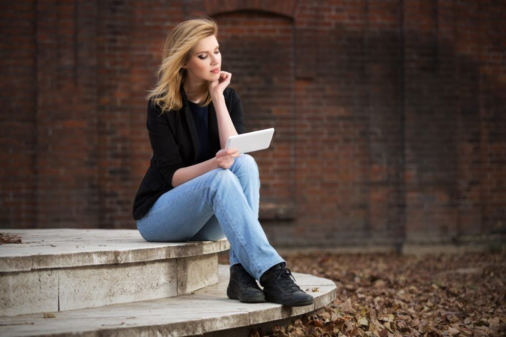 a blonde woman sitting outside, reading a letter