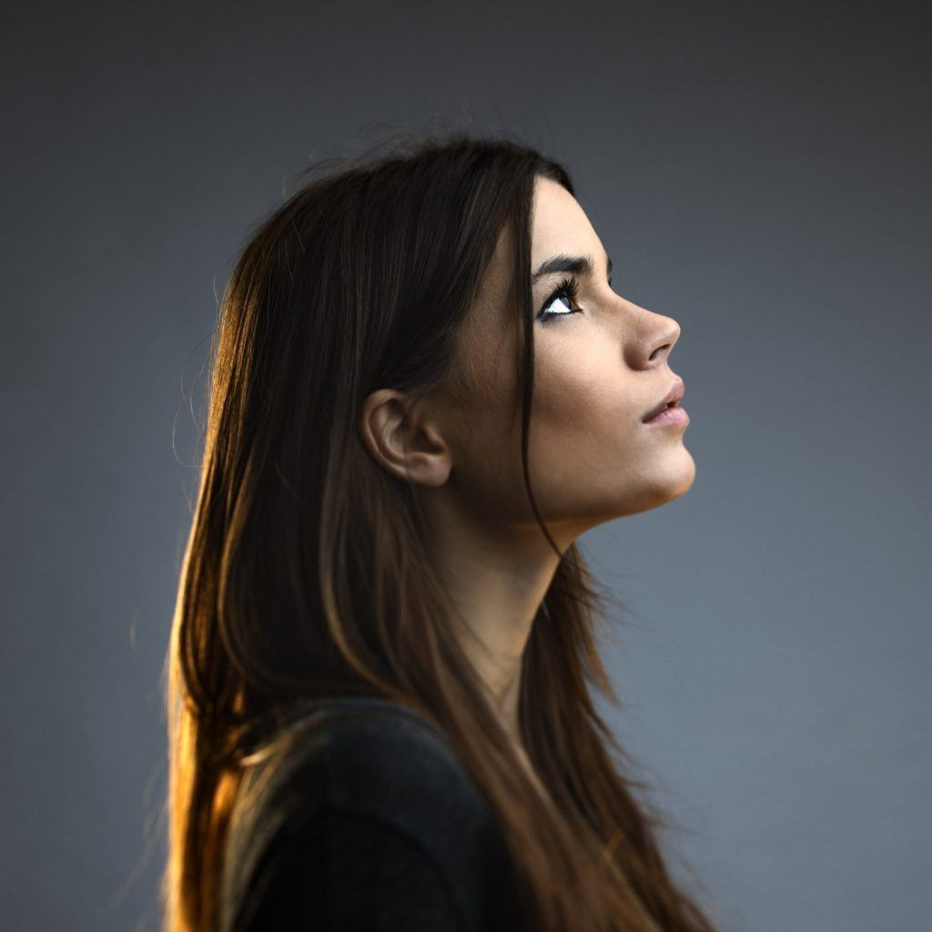a side view of beautiful woman on grey background