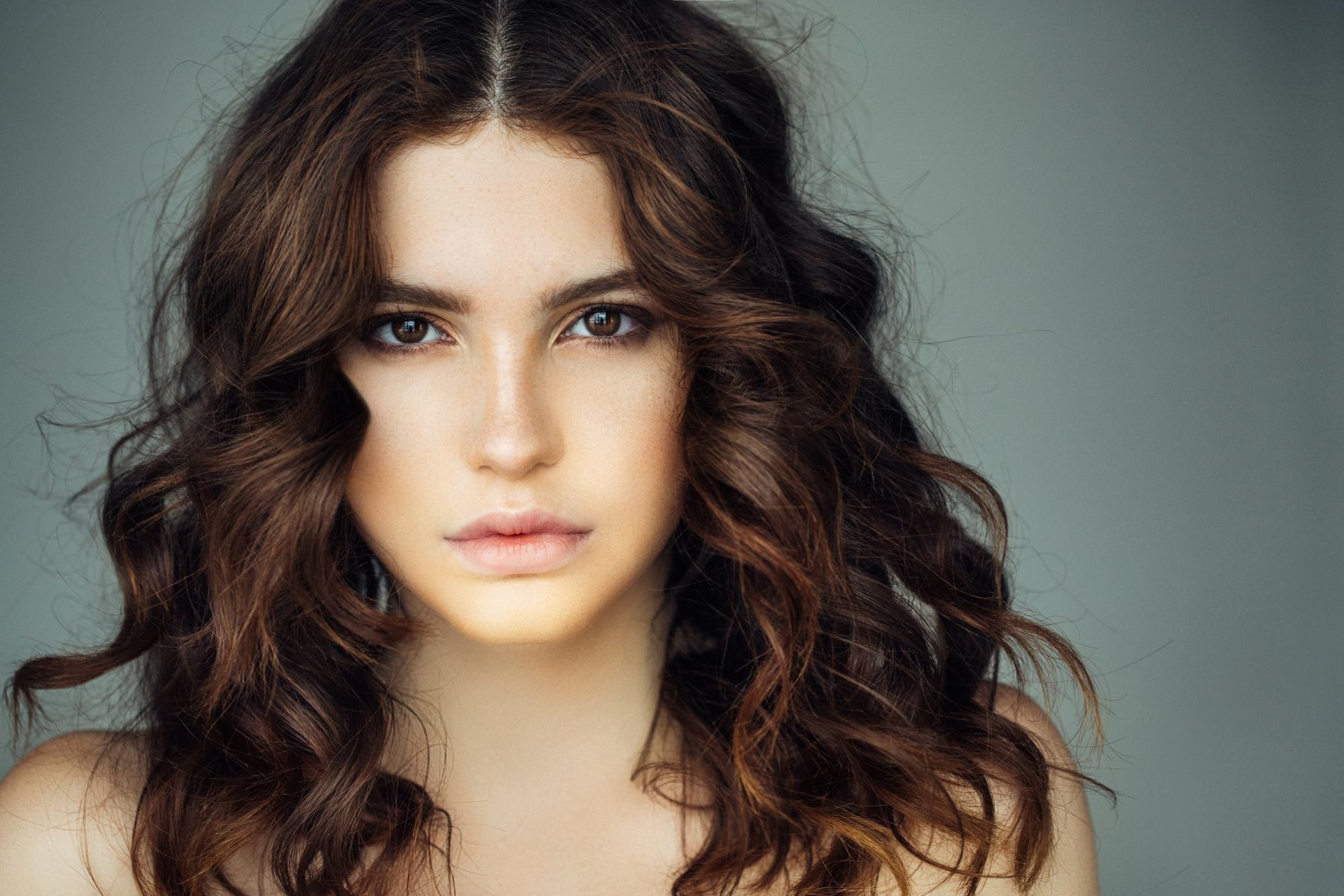a closeup look of wavy hair beautiful girl on grey background