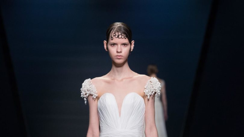 a photo pf female fashion model in a white wedding dress walking on the catwalk with artsy bangs on her hair