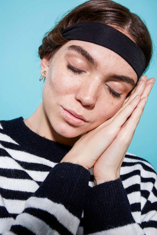 a woman wearing hair band sleeping on her hands