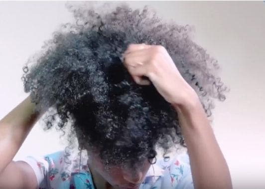 an afro woman looking down and styling her hair