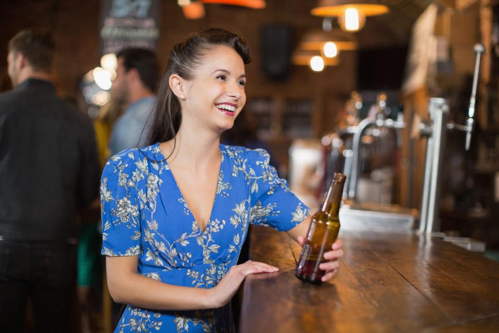 a waoman with long dark hair in a floral blue dress sitting on the bar holding a bottle of beer