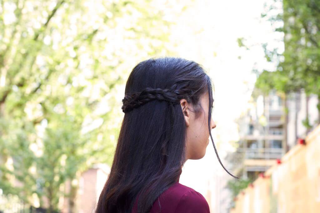long dark haired model with a half-up, half-down hairstyle braided crown