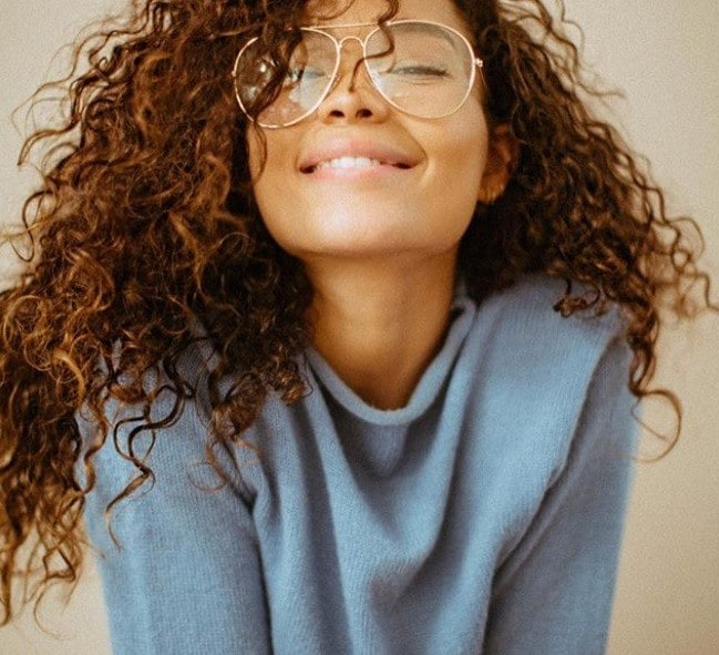 Food for healthy hair guide: Woman with healthy long natural curly hair, wearing a blue jumper and smiling