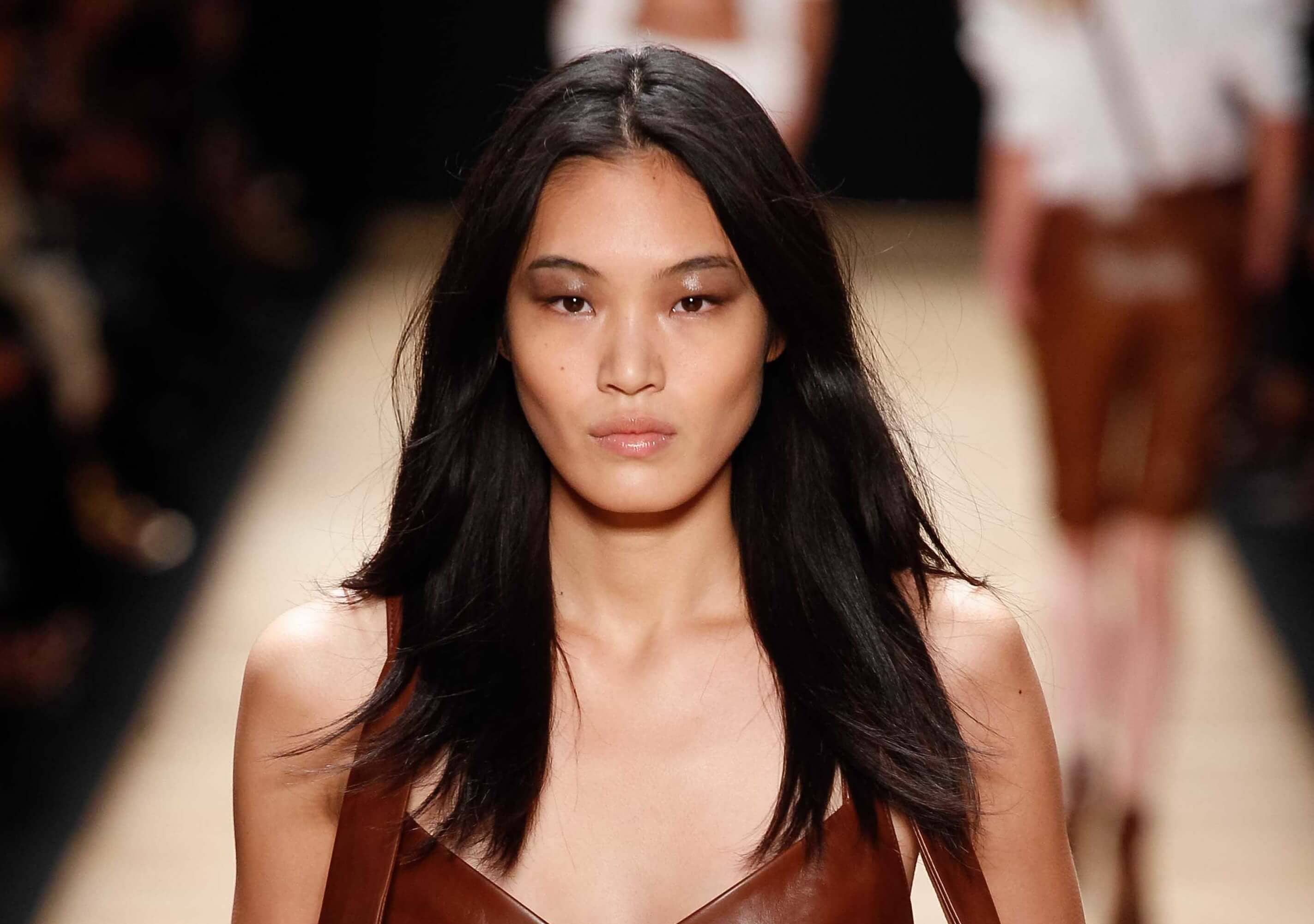 Asian hairstyles: Asian woman with dark brown hair with layers on runway.