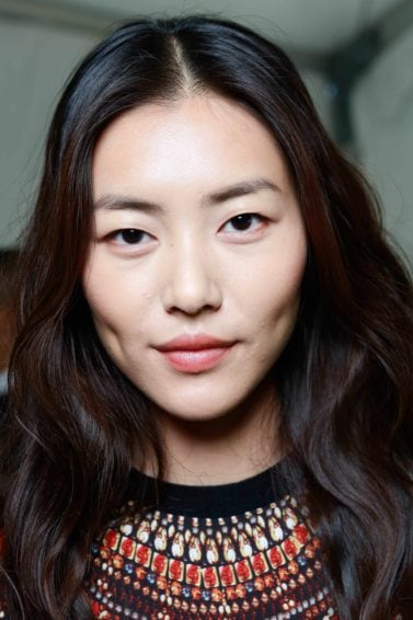 the best anti frizz serum: Young Asian model with wavy long dark brown hair from the DVF SS14 catwalk