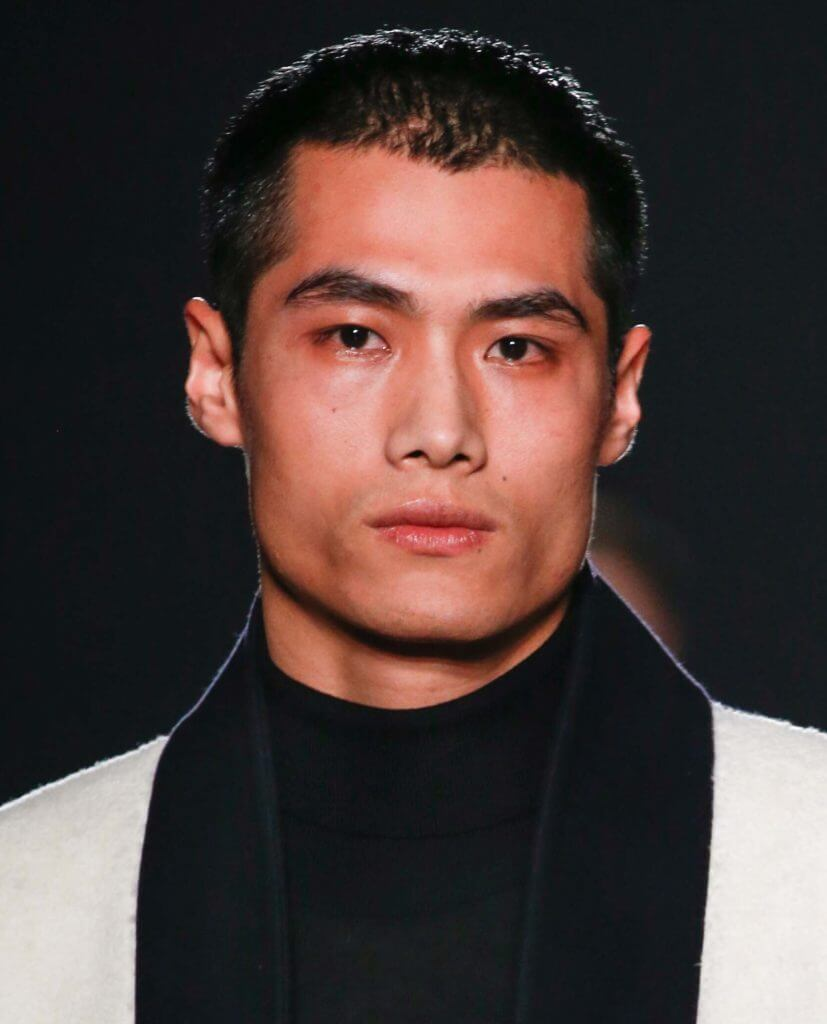 asian man on the runway with dark hair worn in a ceaser cut
