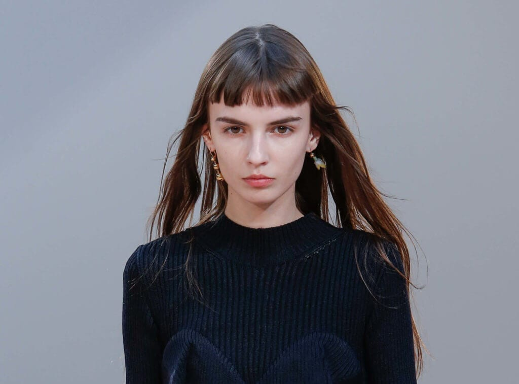 woman on the runway with a micro bangs hairstyle on long brown hair