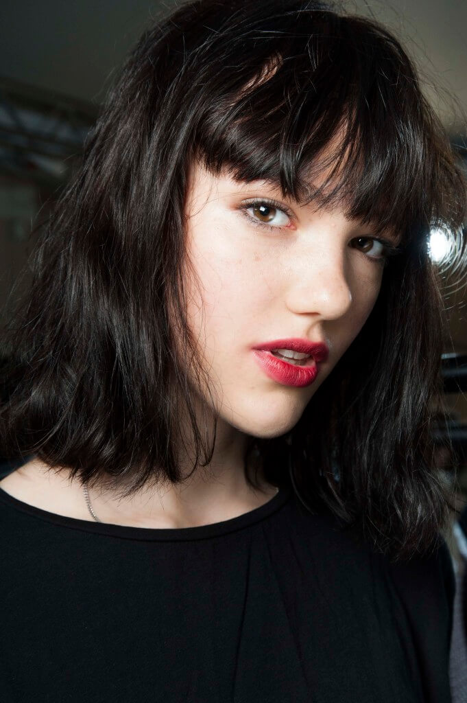 woman with dyed black hair worn in a wavy bob and a choppy fringe