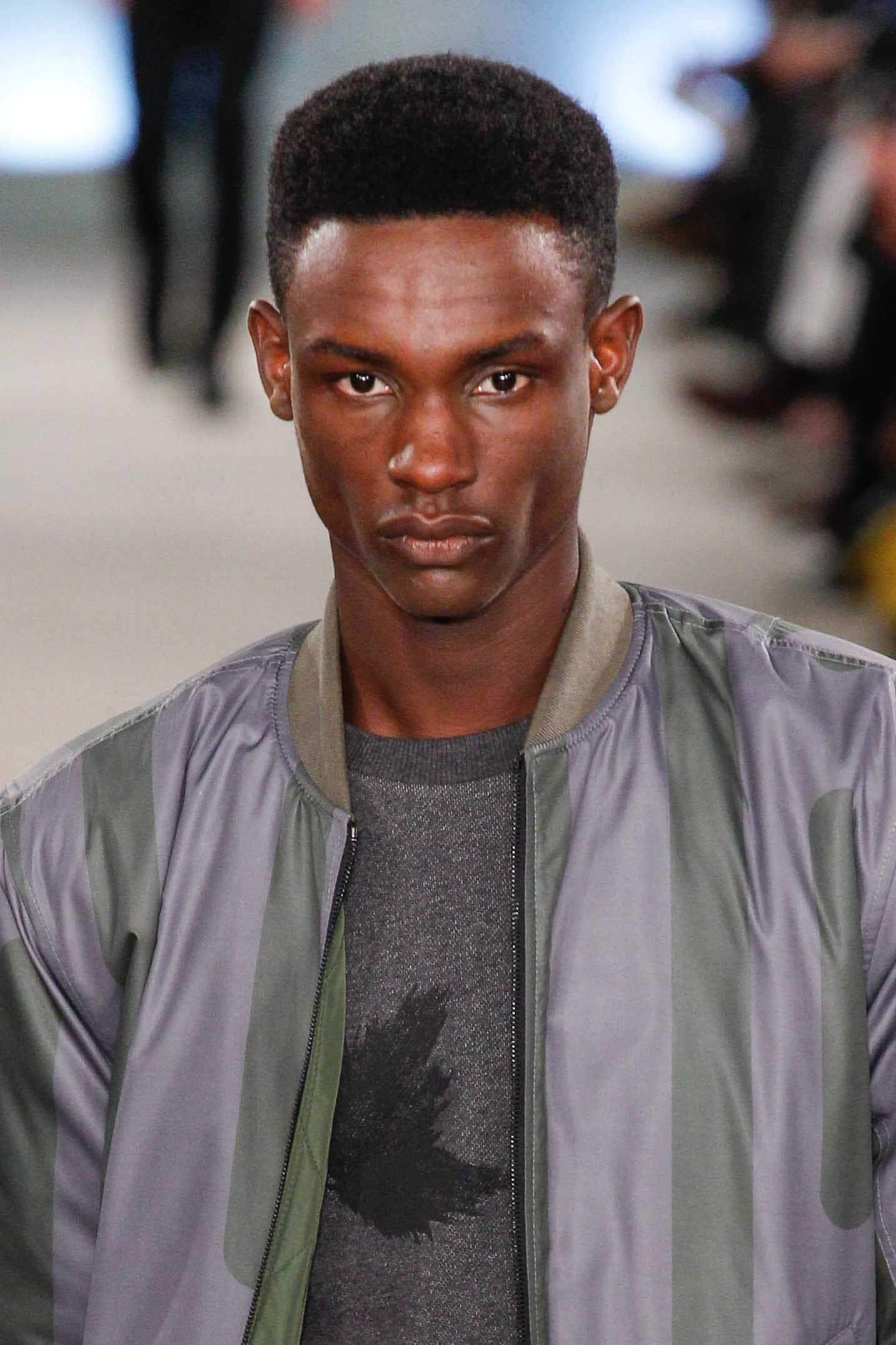 High top fade: Black man on runway with fade haircut wearing a silver grey jacket