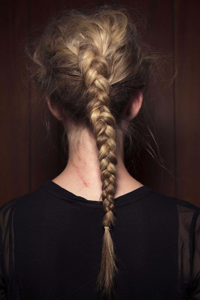 the back view of a blonde woman with a Dutch braid