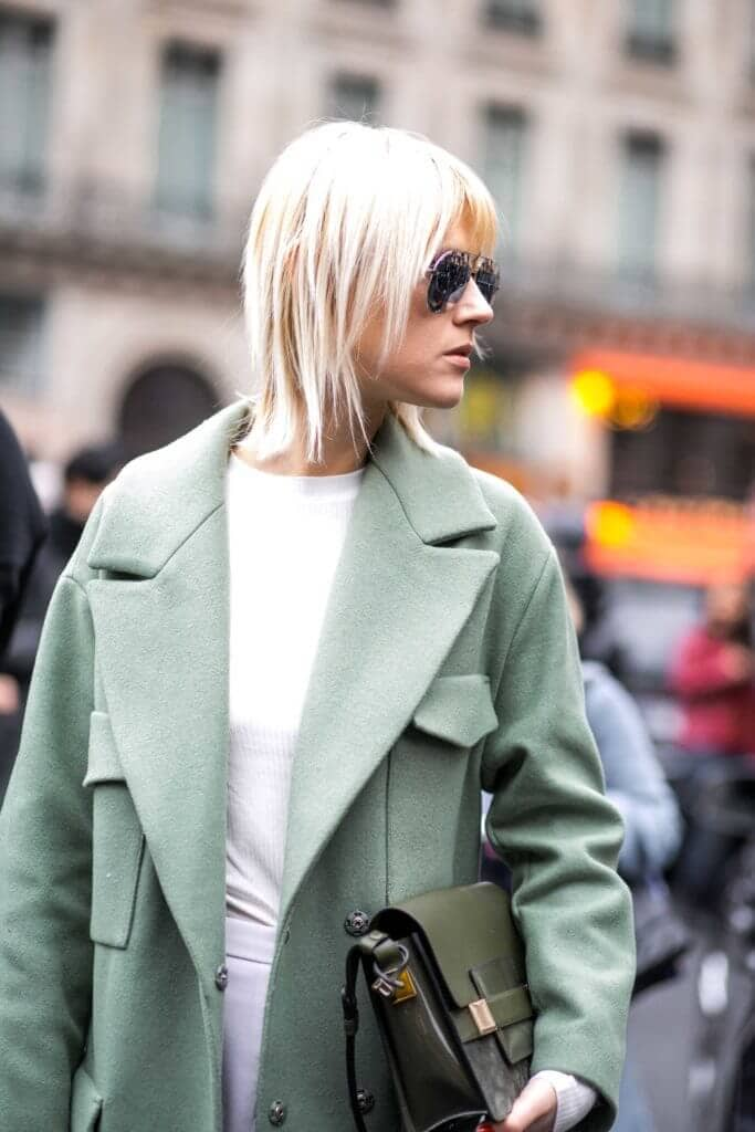side view of a woman with white hair, a green coat and sunglasses