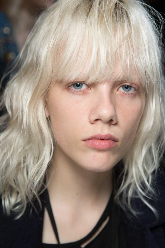 Blonde hair: Front facing image of a woman with platinum blonde hair and a full fringe.