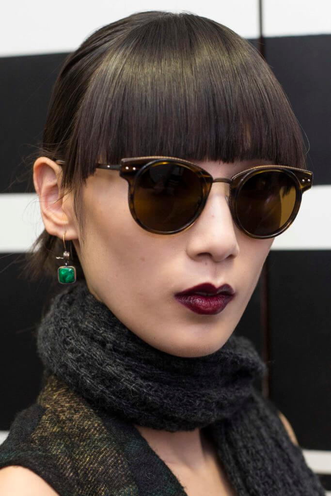 woman with dark brown hair and a blunt fringe wearing sunglasses