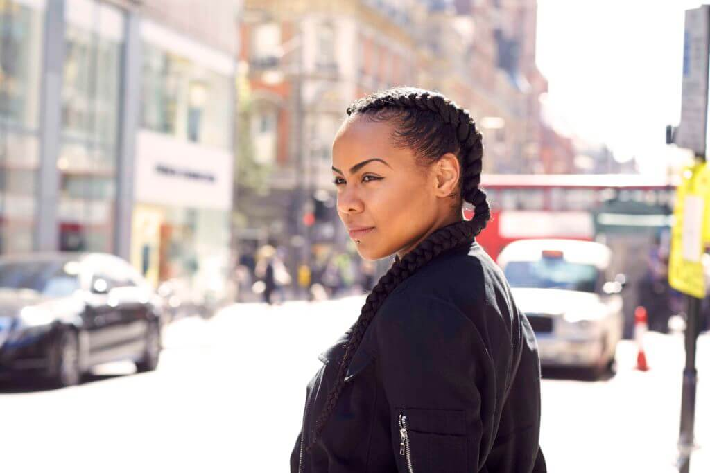 hairstyles for black women: close up shot of a woman with dark brown natural hair styled into long cornrow pigtails, wearing black and posing on the street