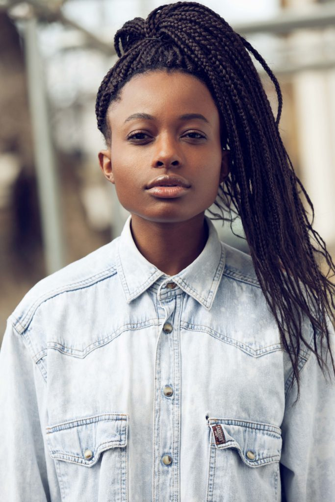 Styles for box braids: young black woman wearing a shirt with box braids put into a high ponytail