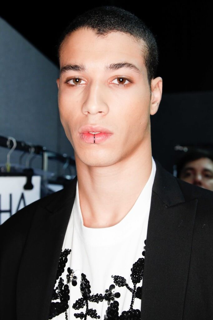 man with dark hair worn in a buzz cut backstage at a fashion show