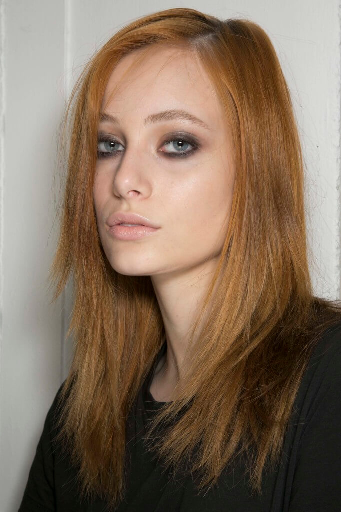 model with light ginger copper hair and long layered hair