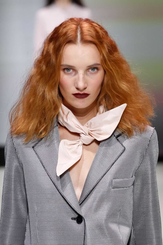 model on the runway with muted orange hair and voluminous waves