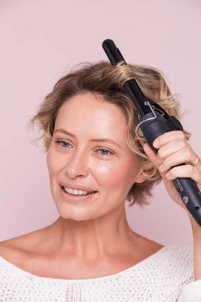 model with short blonde brown hair using a curling iron to curl her hair