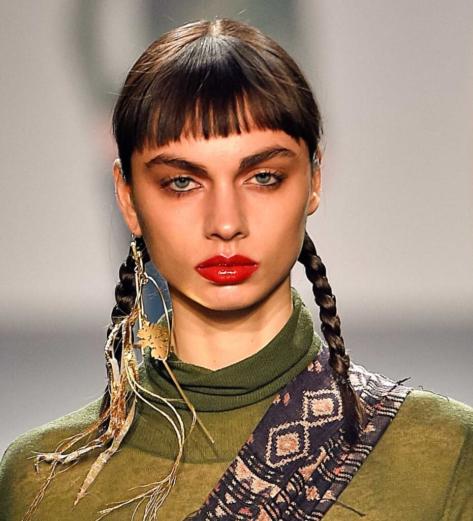 woman on the runway with dark brown hair in braided pigtails with a fringe