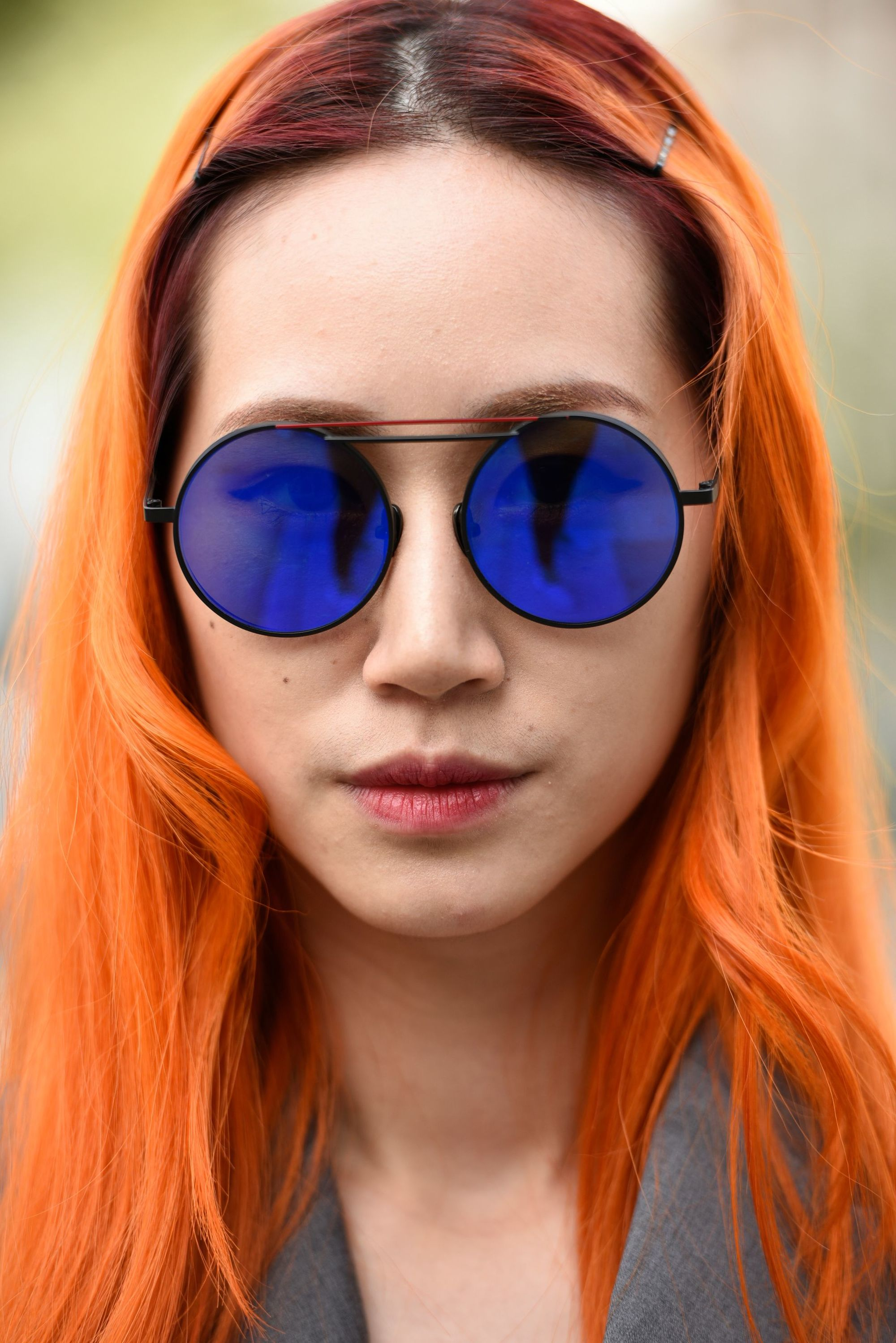 Does dyeing your hair damage it: Woman with long orange hair, wearing circle sunglasses and posing for a street style shot