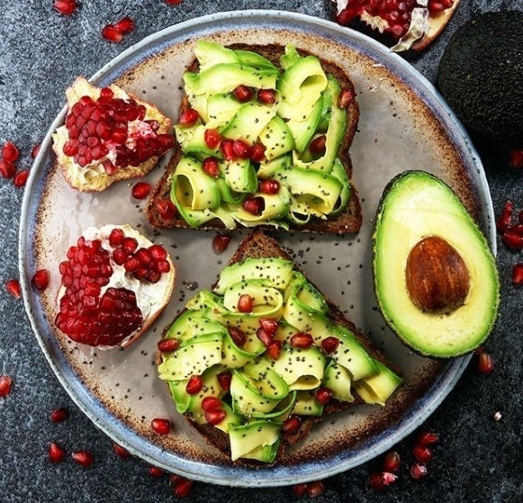 Food for healthy hair guide: Flat lay shot of avocado toast with pomegranate seeds scattered around