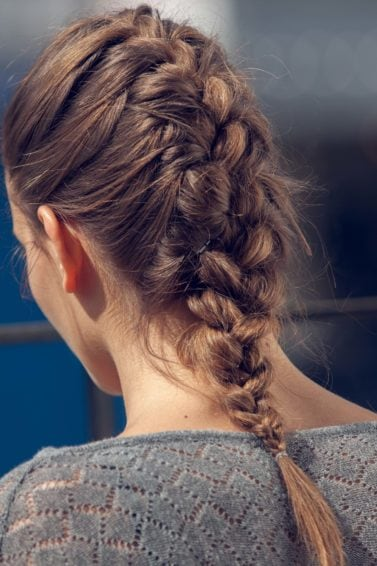 updo for medium hair: French braid hairstyle back view brunette with medium-length hair and a classic French plait